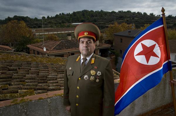 Alejandro Cao in piedi vicino a una bandiera nordcoreana